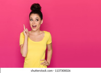 Happy beautiful young woman in yellow top is pointing up, looking away and talking. Waist up studio shot on pink background.