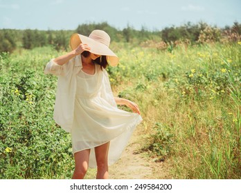 Happy beautiful young woman in yellow dress and hat with wide brim walking in summer park