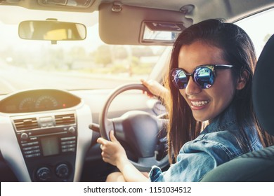 Happy beauty asian woman black hair smile with sunglass and Blue jean jacket driving car at sunset. Picture with filters and instagram effects