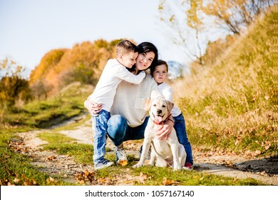 happy beauty family mother and two young sons smiling and sitting on road in park in autumn, boys with mom and dog