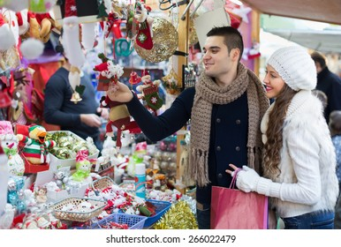 Happy beauty girl with boyfriend choosing Christmas decoration at fair. Focus on man
