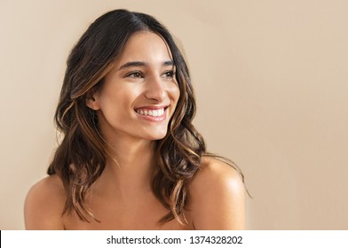 Happy beauty woman looking away isolated on background. Cheerful young brunette with nude shoulder smiling after skin treatment. Beautiful hispanic girl waiting spa therapy.