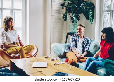 Happy best friends enjoying leisure and funny conversation resting in comfortable apartment.Positive casual dressed young people laughing during game in modern flat.Hipsters spending time together