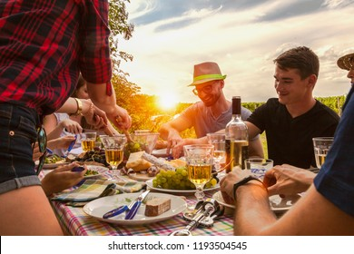 happy best friends have an al fresco party in the garden. they enjoy a meal of simple finger food with fresh white wine and rose wine. rustic farm life concept after harvest work.