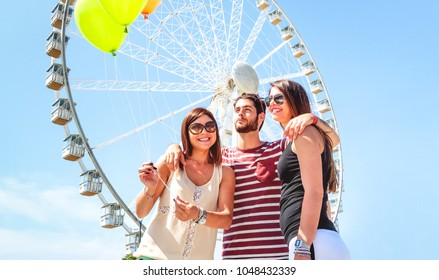 Happy best friends having fun on spring break holiday - Cheerful students on tour at ferris wheel - Joyful teenagers on summer vacadation day  - Concept of travel friendship , youth  and togetherness