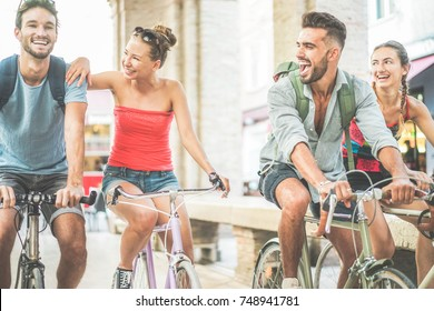 Happy best friends riding bicycles in city center - Young students having fun together around the town - Youth and friendship concept - Soft focus on left woman face - Warm filter