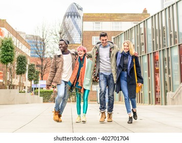 Happy best friends walking in London city with St Mary Axe (The Gherking) in urban background. Group of multiracial happy people embracing each other in social situation. Hipster person with style.