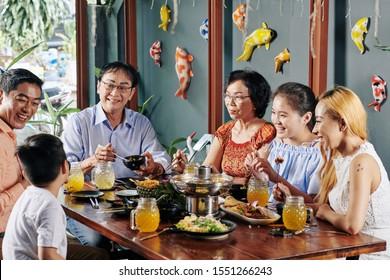 Fröhliche große asiatische Familie spricht, lacht und isst gutes Essen beim Abendessen