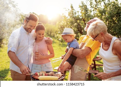 Happy big family gathered around the grill at picnic.Leisure,food,family and holidays concept.