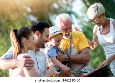 Happy big family gathered around the grill at picnic. Leisure,food,family and holidays concept.