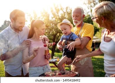 Frohes Großfamilienhaus, das sich bei Picknick um den Grill versammelt hat.
