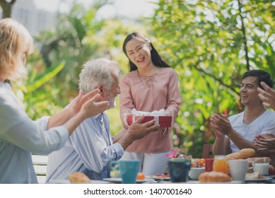 Happy big family have a lunch at outdoor in green garden. Grand father's birthday party on picnic table in summer. The Asian woman give gifts to old Europe man. Big family outdoor lunch party concept.