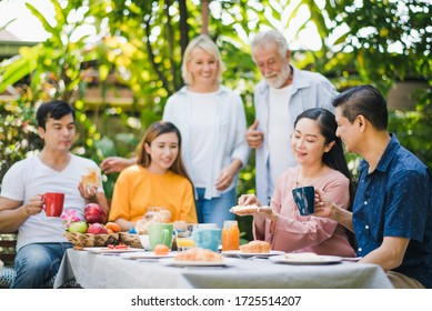 Happy big family have a lunch at outdoor in green garden. Lunch or tea time on picnic table in summer. Old woman make a bread with Fruit jam to give husband.  Big family outdoor lunch concept.