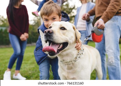 Happy big family with labrador retriever dog having fun together in park
