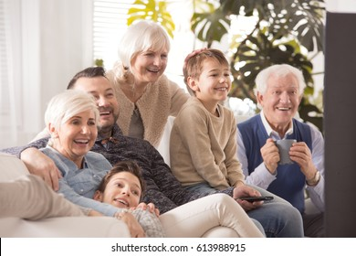 Happy big family sitting on sofa and watching tv together