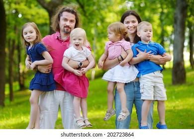 Happy big family of six having fun at summer park on beautiful sunny day
