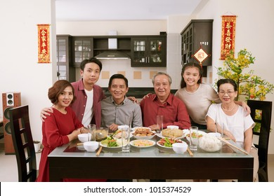 Happy big Vietnamese family having Tet celebration dinner. Scrolls wishing luck and wealth in the background
