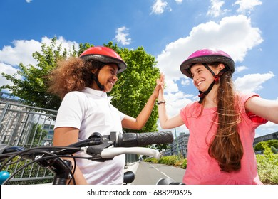 Happy bike riders giving high five after racing