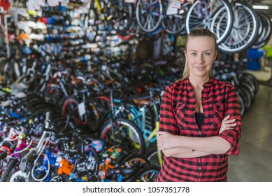 Happy bike shop owner. Bike store. Bike shop owner stands proudly in front of his stock.Saleswoman in bicycle shop