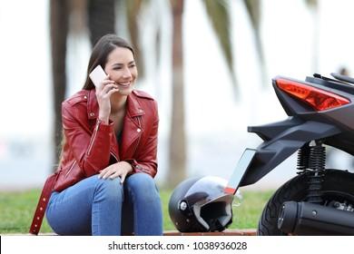 Happy biker calling insurance on phone beside her motorbike on the street