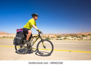 Happy biker relax on beautiful road in Israel desert. Sunny hot day