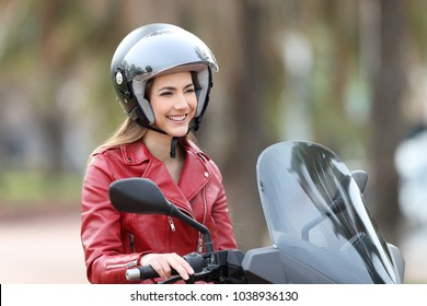 Happy biker sitting on a motorbike looking away on the street