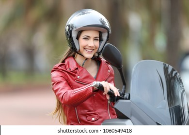 Happy biker wearing an helmet sitting on her motorbike looking at camera on the street