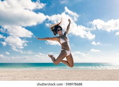 Happy bikini woman jumping of joy on beach. Tropical vacation travel destination.