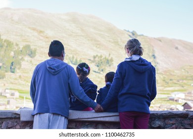 Happy biracial family. Caucasian mom and native american dad holding hands. Their two children sitting on the wall and admiring the beauty of nature.