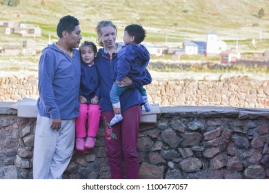 Happy biracial family. Caucasian mom and native american dad with their two little children in the countryside. The concept of parenthood.