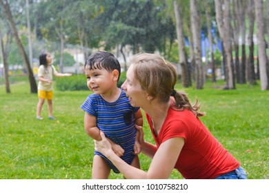 Happy biracial family - caucasian mommy hugging her little latin son in the summer park.