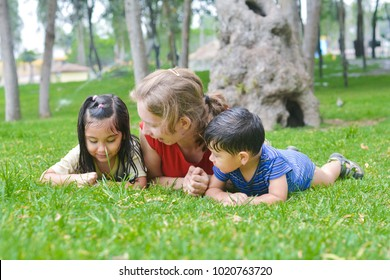 Happy biracial family in the summer park - caucasian mother with her little latin children laying on the grass.