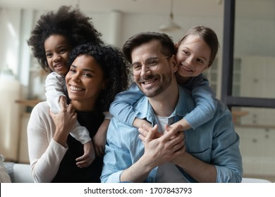 Happy biracial girls hug piggyback smiling young multiracial parents enjoy weekend at home together, overjoyed small multiethnic daughters embrace play with loving mom and dad on quarantine