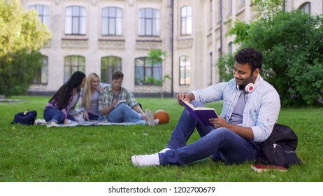 Happy biracial male student sitting on grass and reading interesting book