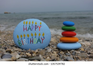 Happy Birthay message carved and colored on a stone with multi colored pebbles on the beach