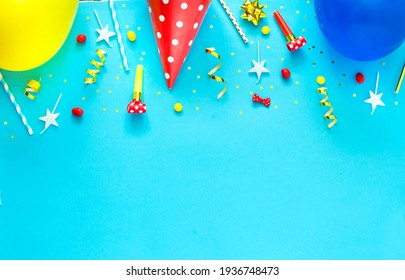 Happy birthday background: party hat, balloons, flute, serpentine, stars, cocktail tubes, blower on a blue background. Holiday concept Copy space