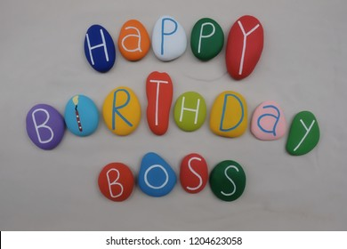 Happy Birthday Boss with colored stones over white sand