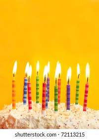 happy birthday cake shot on a yellow background with candles and lots of space