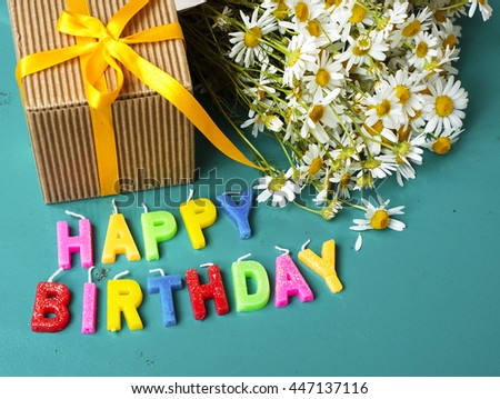 Happy Birthday Candles With Chamomile Flowers And Gift Box On Blue Background Place For The