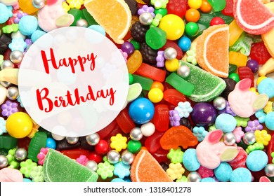 Happy Birthday card. Assorted variety of sweet sugar candies includes gummy bears, Easter bunny candy, gum balls and sugar fruit slices. Candy flat lay background.