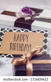 Happy Birthday card with giftsin black, white and gold colors.