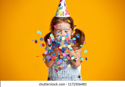 happy birthday child girl with confetti on  colored yellow background