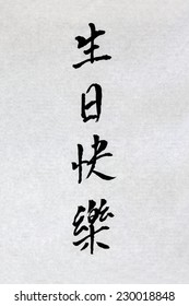Happy Birthday chinese calligraphy script on rice paper. Translation reads as happy birthday.