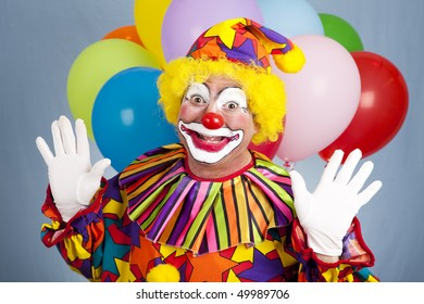 Happy birthday clown with balloons, holding his hands in a surprised gesture.