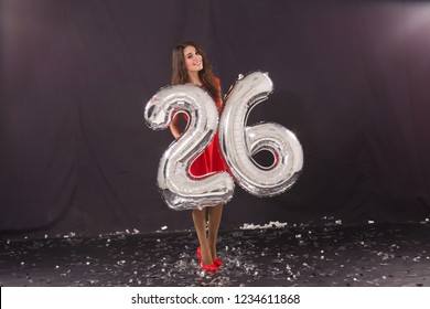 Happy birthday concept - Beautiful young woman with number-shaped 26 balloons