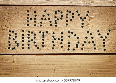 Happy Birthday congratulation made as text of bullet holes in wooden boards