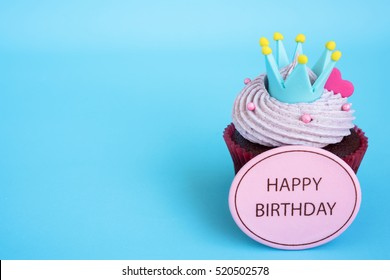 Happy birthday cupcake with crown and pink heart over blue background with copy space