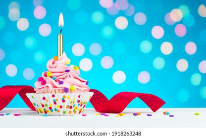 Happy Birthday cupcake. Tasty cupcakes with pink cream icing and colored sprinkles. Burning candle in a cake. Sweet delicious dessert on white wooden table and blue background with bokeh. Copy space.