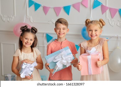 Happy birthday Happy cute children in festive decor and beautiful dresses with gifts in their hands.
