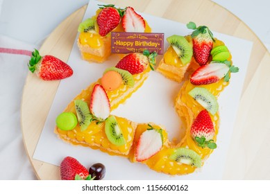 Happy birthday fresh fruit cake with Chocolate tag Number cake concept with strawberry kiwi fruit cake.